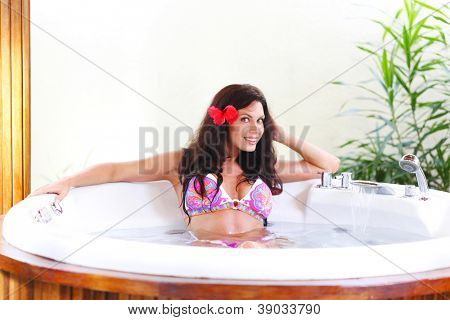 Pretty woman relaxing in jacuzzi of tropical hotel