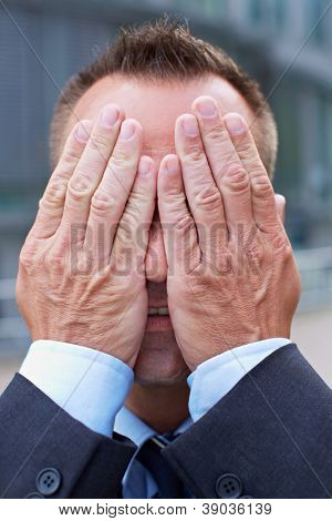 Business man covering his face with his both hands