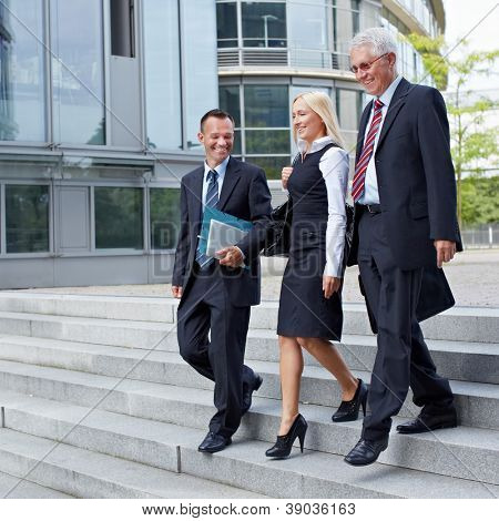 Three happy business people walking together outside
