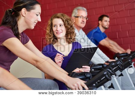 Female fitness trainer helping woman on bike in fitness center