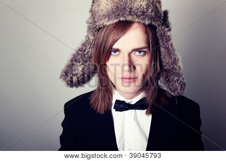 Young trendy man handsome in suit with bow tie and fur hat, sexy guy with long fair hair looking at camera studio shot
