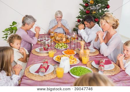 Family saying grace together before christmas dinner