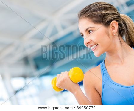 Gym woman exercising lifting free weights and smiling