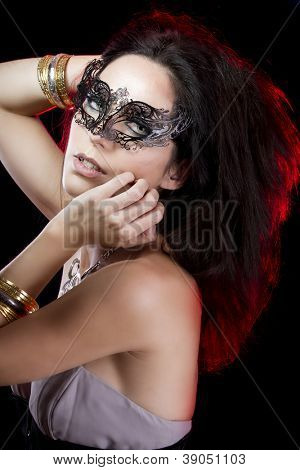 Sexy woman with bracelets of gold and silver, venetian mask with red light