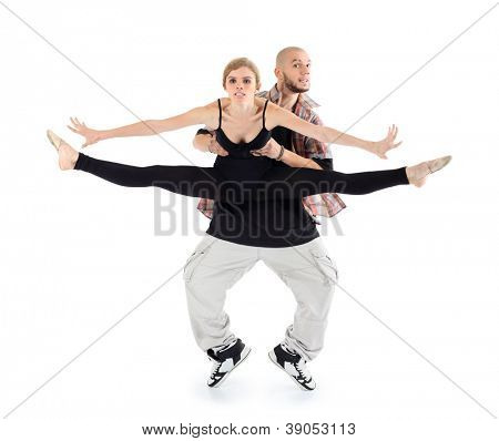 Breakdancer holds ballerina in black and stands on tiptoes isolated on white background. Woman stretched legs in twine and spread her arms to sides.