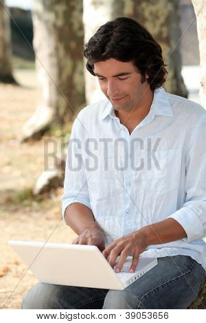Man in park using laptop
