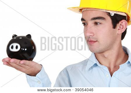 young architect looking at piggy bank