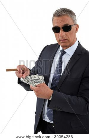 Businessman with a cigar and a fistful of dollars