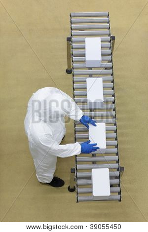 aerial view of  worker in white uniforms working with boxes on packing line