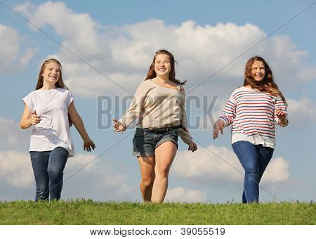 Three smiling girls run at green grass at background of blue sky.