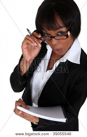 portrait of black businesswoman looking upwards holding pen and notepad