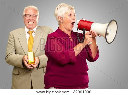 Senior Woman Shouting In Megaphone In Front Of Businessman Holding Gold Bar On Gray Background