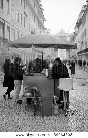 RUA AUGUSTA, LISBON, PORTUGAL - 02 NOVEMBER 2012 - A street roasted chestnut seller plies his trade