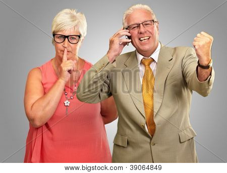 Man Taking On Cellphone In Front Of Woman Gesturing On Grey Background