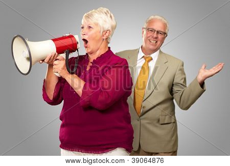 Senior Woman Shouting In Megaphone In Front Of Businessman On Gray Background