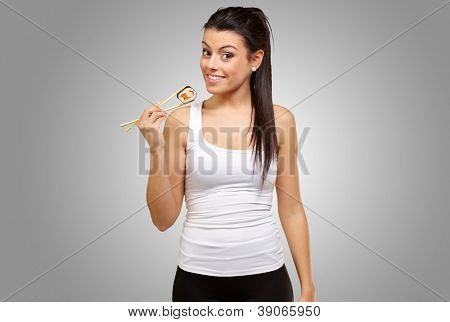 Young girl Holding Sushi Roll with chopsticks isolated on gray background