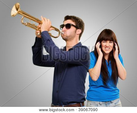 Man Blowing Trumpet In Front Of Frustrated Woman On Gray Background