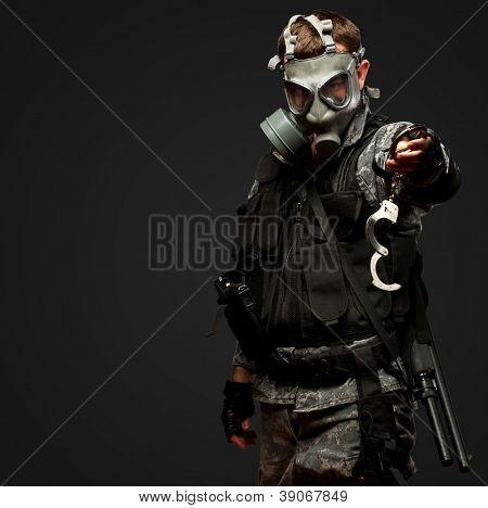 Soldat mit A Gasmaske Holding Handschellen vor einem schwarzen Hintergrund