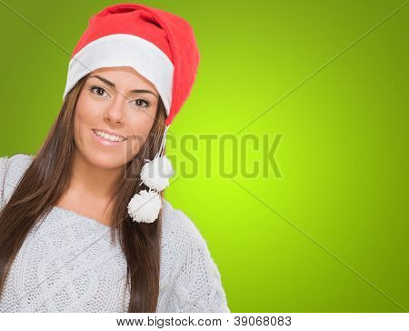 Happy woman wearing a christmas hat against a green background
