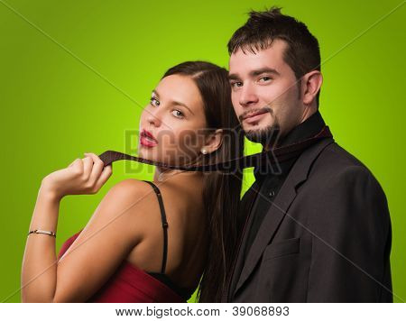 Beautiful Woman Holding Businessman Tie against a green background