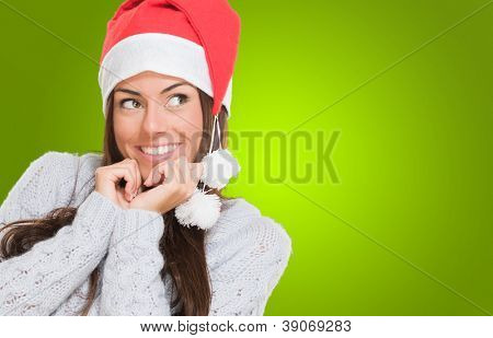 Woman wearing a christmas hat and thinking against a green background