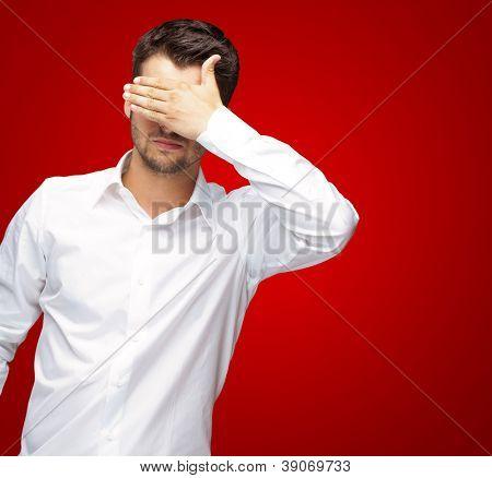 Retrato de um homem de negócios cobrindo olhos isolados em fundo vermelho