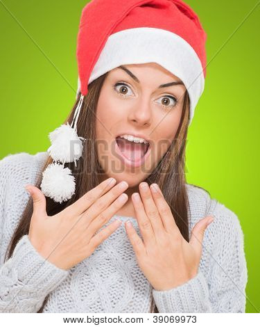 Surprised woman wearing a christmas hat against a green background