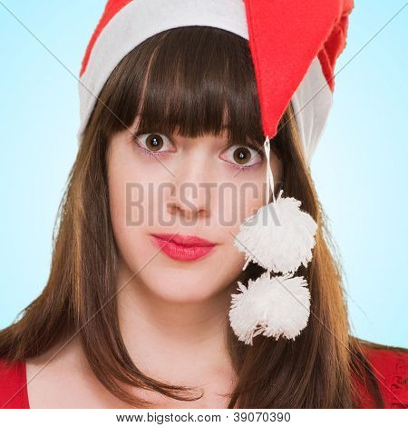 confused woman wearing a christmas hat against a blue background