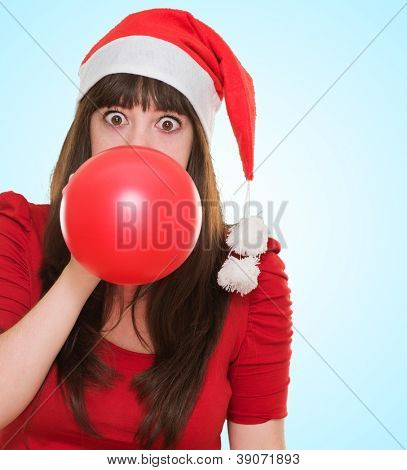 woman blowing balloon and wearing a christmas hat against a blue background