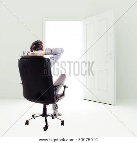 business man in a chair in front of open door