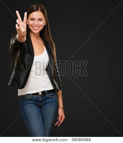 Beautiful Woman Giving Victory Sign against a black background