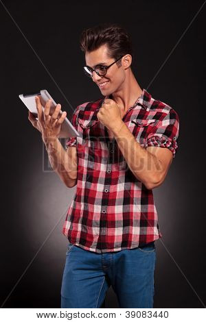 side view of a fashion man reading on a tablet and winning