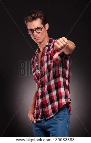 handsome young man with thumbs down on a dark background