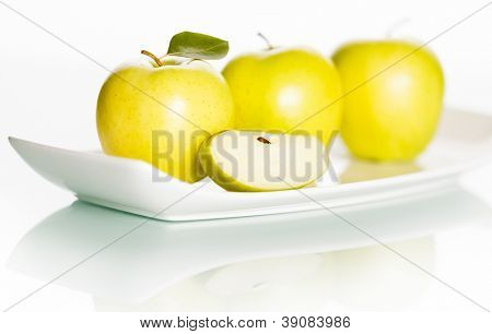 Fresh green golden delicious apples and slice on elegant plate isolated on white background.