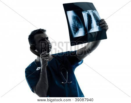 one caucasian man doctor surgeon radiologist medical examaning lung torso  x-ray image silhouette isolated on white background