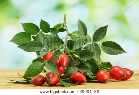 ripe hip roses on branch with leaves,  on wooden table on green background