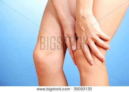 woman holding sore knee, on blue background
