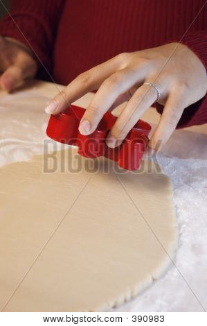 Woman's Hand Making Cookie Cutouts