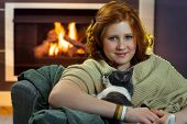 image of fondling  - Teenage girl sitting at fireplace fondling cat - JPG
