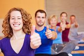 Happy attractive woman in fitness center holding her thumbs up