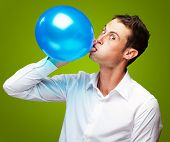 Portrait Of Young Man Blowing a�?� Balloon On Green Background
