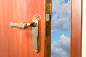 stock photo of door-handle  - Door opening to the blue sky with clouds - JPG