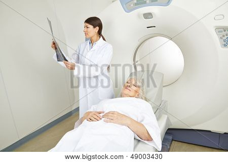 Doctor looking at x-ray image of senior patient at MRI therapy