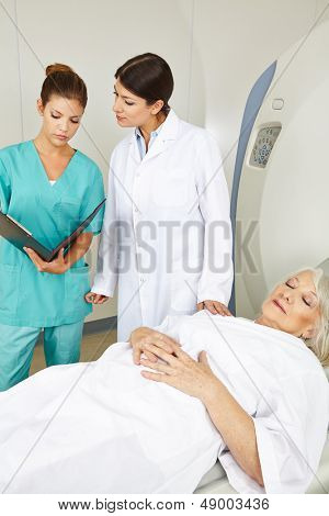 Doctor and nurse looking at medical records of senior patient at MRI