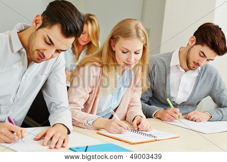 Group of students studying together in university class