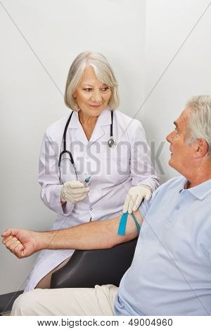 Doctor withdrawing blood from senior patient with a syringe in a hospital