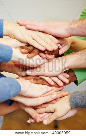 Team stacking many hands on top of each other for motivation