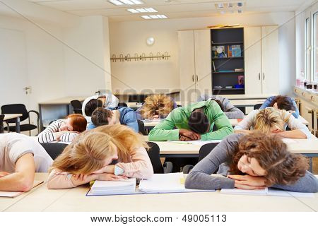Many tired students sleeping in classroom with their heads on the table