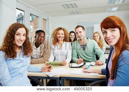 Many smiling students in university class working as a team