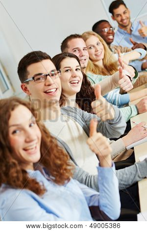 Many happy successful students holding their thumbs up in class